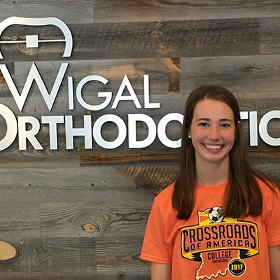 Female patient posing in front of Wigal Orthodontics sign