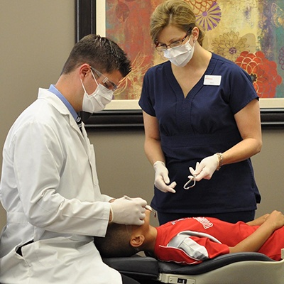 Orthodontist and assistant treating patient