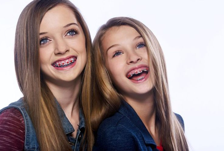 Two girls with red bracket braces