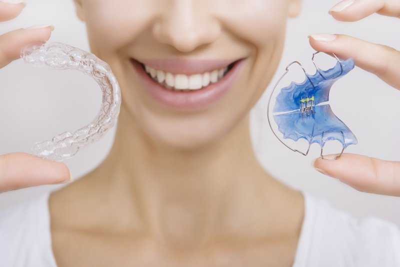 Woman smiling and holding retainers