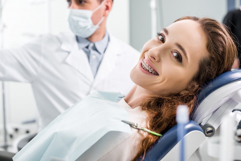 Adult smiling with braces at orthodontist appointment