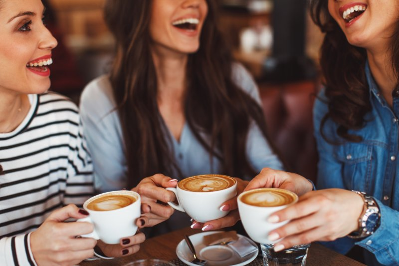 Group of women smiling over cup of coffee