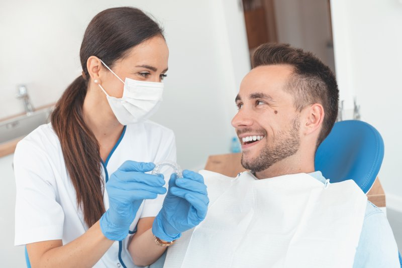Smiling orthodontist and patient discussing Invisalign