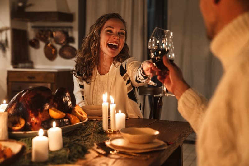 Woman smiling with friend at holiday dinner